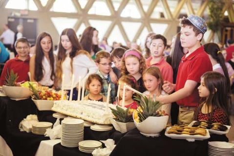 Joshua Chynoweth, 13, of Livonia lights a candle on the anniversary cake.